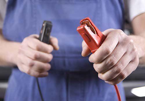 Un meccanico regge un paio di pinze per batterie auto