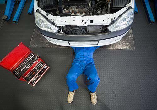 Meccanico all'opera mentre revisione un auto e cassetta degli attrezzi rossa