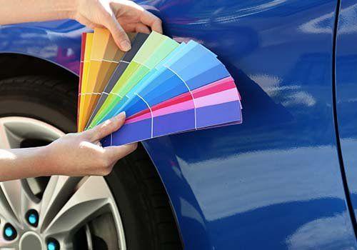 Una mano che regge dei campioni di diverso colore per scegliere la verniciatura dell'auto