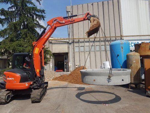 una gru che alza un pezzo di cemento circolare