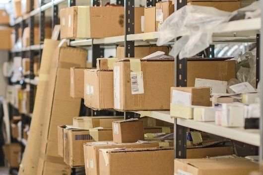 packages sitting on a shelf in a mail room