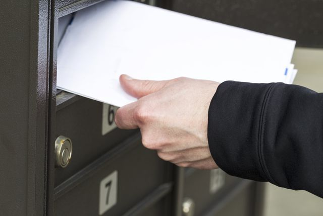 close up of placing mail in a mailbox