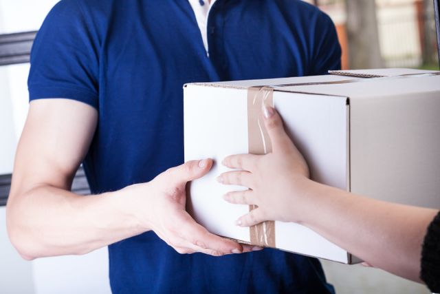 woman handing package to post office worker