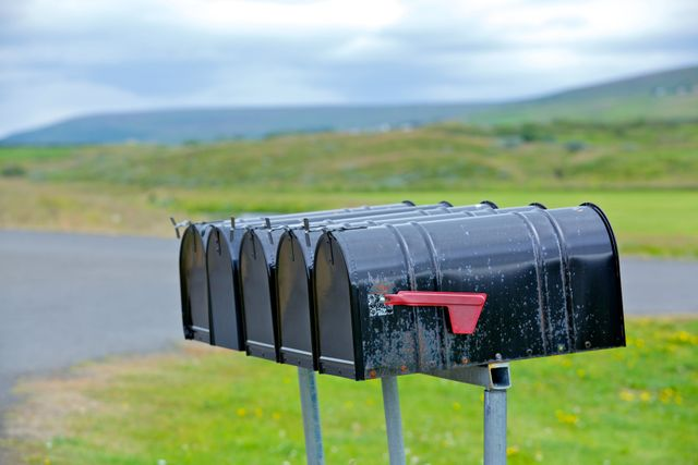 several mailboxes in a row on an empty road