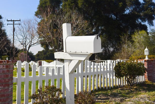 white mailbox and white fence