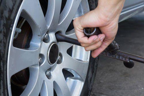 una mano con una chiave che svita il bullone di una ruota