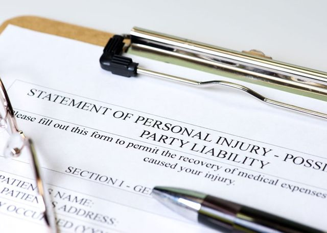 Personal injury claim on clipboard with pen and glasses
