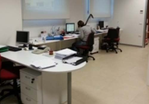 un ufficio con delle scrivanie e una ragazza al pc