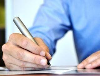 Primo mano mano che impugna una penna e firma documento