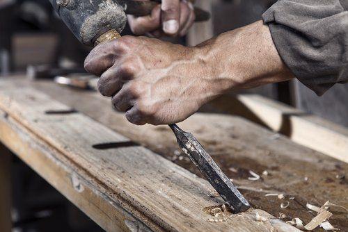 Un falegname intaglia una trave in legno