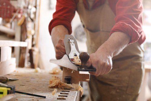 Falegname pialla un pezzo di legno