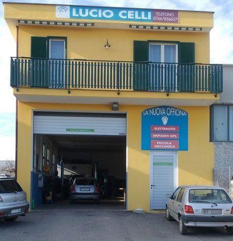 vista di una palazzina gialla con sotto un'insegna Lucio Celli La Nuova Officina e sotto l'entrata all'officina