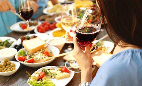 Donna beve il vino durante un pranzo all'aperto
