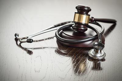 Gavel and medical stethoscope on table
