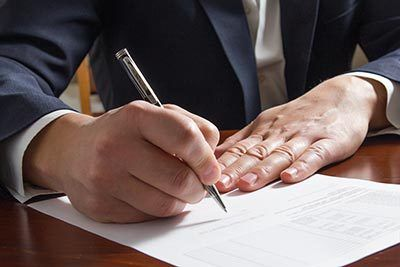 Close up hands of experienced lawyer signing paperwork