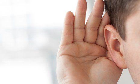 una mano vicino a un orecchio