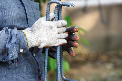 costruttore con dei guanti ed in mano alcuni attrezzi da lavoro