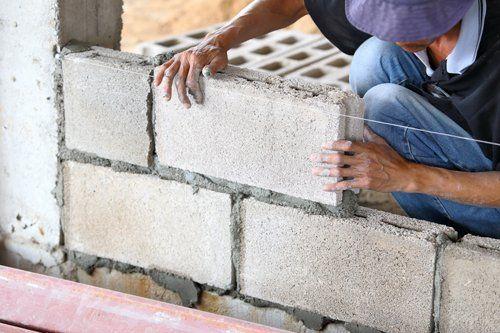un costruttore che mette assieme dei mattoni per un muro