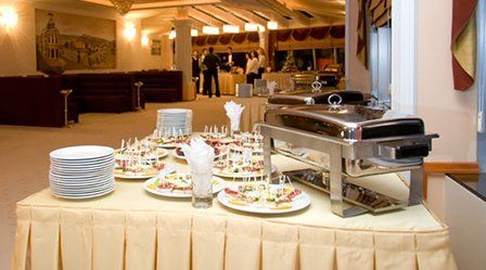 A table set up with hot and cold buffet food and stacks of plates