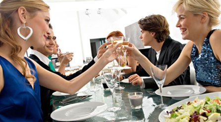 People clinking glasses around a dinner table