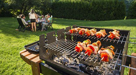 Meat and vegetable kebabs on a barbecue in a garden