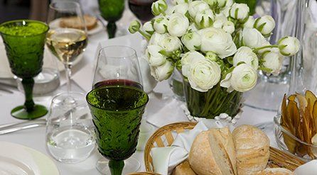 Basket of bread, glasses and a vase of white roses on a table