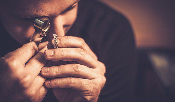 un uomo mentre osserva un anello con una lente di ingrandimento