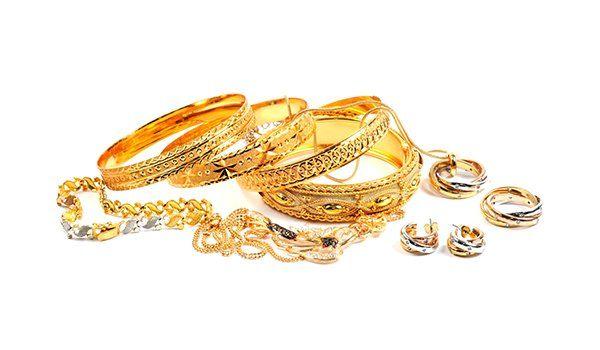 parure di bracciali, anelli, orecchini di oro bianco e oro giallo appoggiati su uno sfondo bianco
