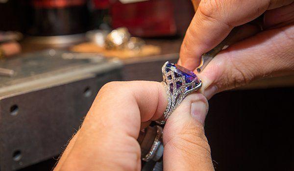 Un gioielliere durante una  lavorazione di un anello di con una  pietra blu e dei brillanti