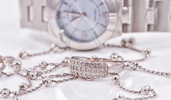 Un anello con dei brillantini, una catena d' oro rosa e un orologio su uno sfondo bianco