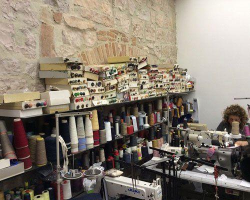 sarta al lavoro all'interno di una sartoria piena di fili e macchine da cucire
