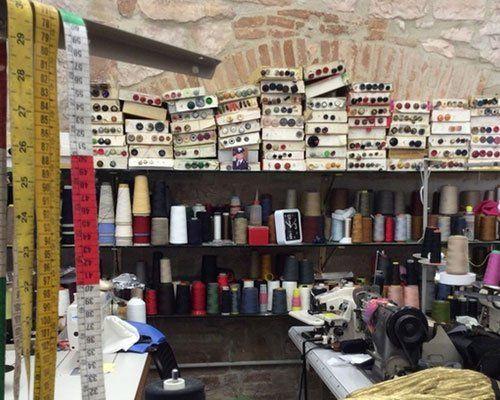 Panoramica dell'interno di una sartoria con diversi tipi di fili di tutti i colori,bottoni,macchine per cucire