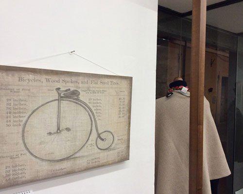 Immagine laterale della vetrina dove si vede un indumento dopo il vetro. Una immagine di un vecchio monociclo appeso nella parete