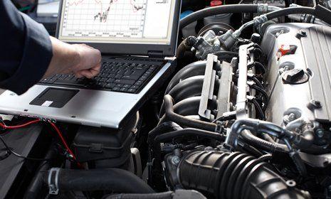 meccanico consulta il omputer sopra il cofano di una macchina aperto