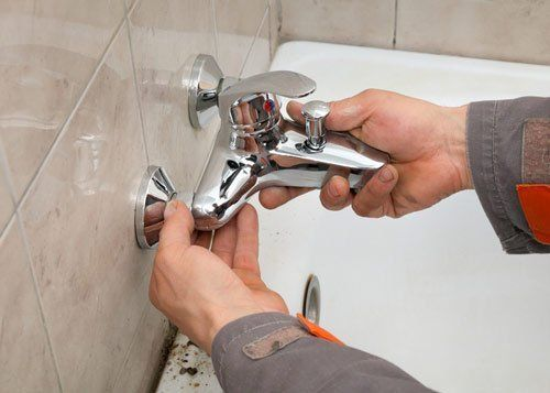 plumber working on bathroom faucet