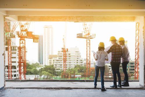 due uomini e una donna con degli elmetti e vista di alcune gru in un cantiere