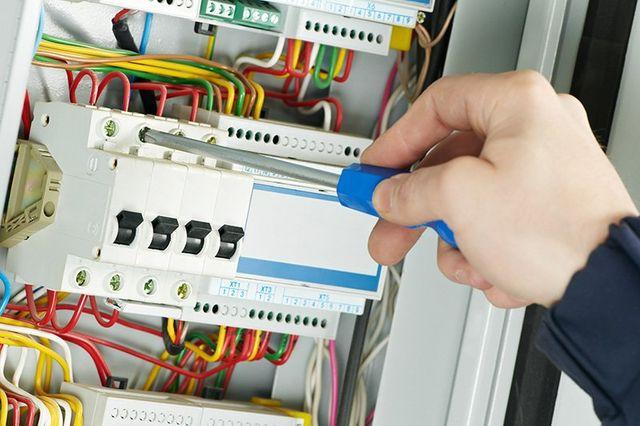 Elettricista al lavoro su un quadro elettrico