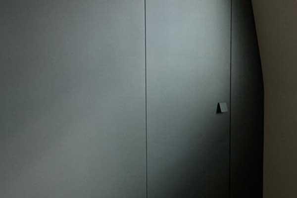 un corridoio con in fondo una porta di ingresso di color bianco con maniglia in ottone e stipiti in legno