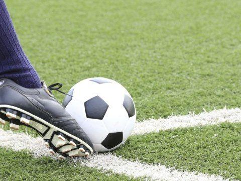 pallone da calcio con piedi di un giocatore sul campo di calcio