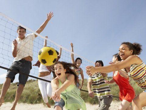 gruppo di amici adolescenti che giocano pallavolo sulla spiaggia