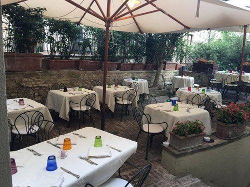 tavoli apparecchiati sotto ombrelloni