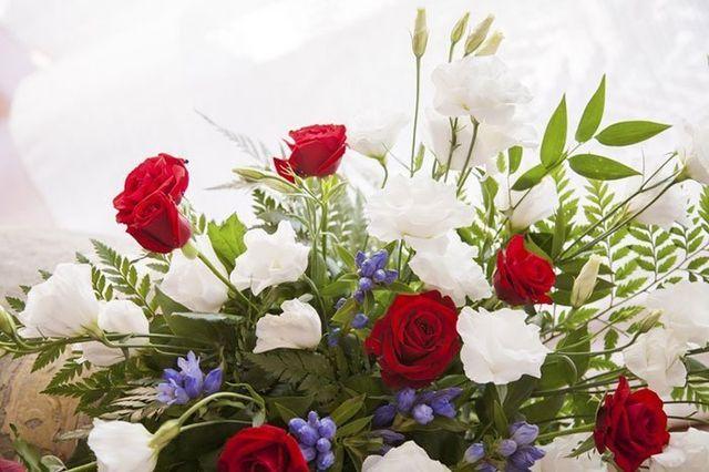 Un bouquet di rose di color rosso e tulipani bianchi su uno sfondo bianco