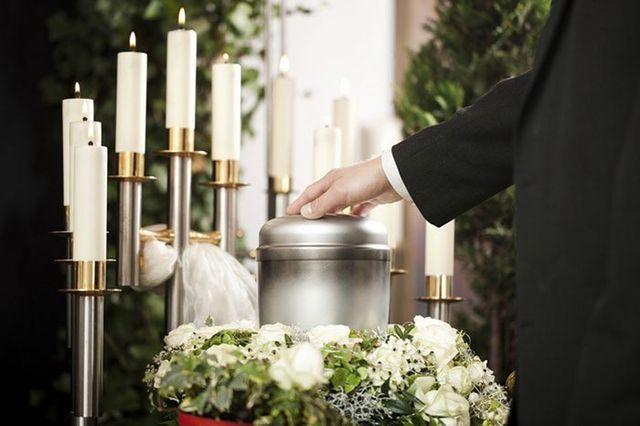 Un uomo con un completo nero che appoggia la mano su un'urna di metallo con dei fiori bianchi e delle candele accese intorno
