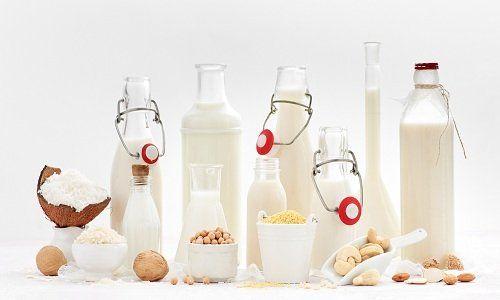 Delle bottiglie di vetro con del latte, delle caraffe e della frutta secca