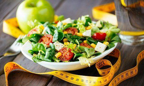 un piatto di verdi misti, pomodori, formaggio dietetico, olio d'oliva e spezie per la salute