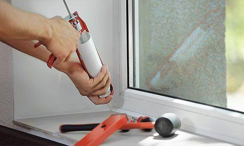 Mettendo silicone per isolare la finestra