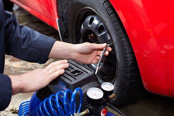 due mani che misurano la pressione di un pneumatico
