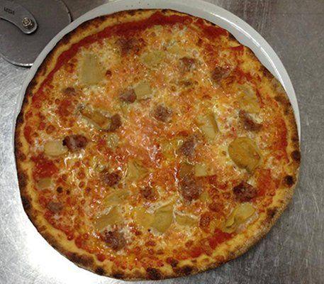Una pizza con formaggio e salsiccia appena sfornata e appoggiata su un piano da lavoro in acciaio