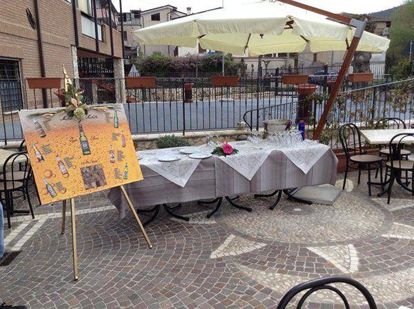 un buffet all'esterno sotto un ombrellone con dei piatti, bicchieri e fiori accanto a un tableau mariage