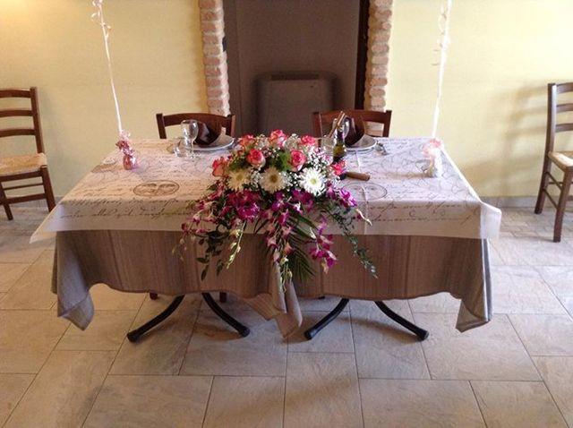 Un tavolo con una tovaglia,un bouquet di fiori, due piatti e due bicchieri